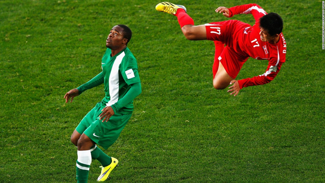 North Korean soccer player Ri Kyong Jin goes flying through the air as he is challenged by Nigeria's Mustapha Abdullahi during an Under-20 World Cup match on Thursday, June 4.