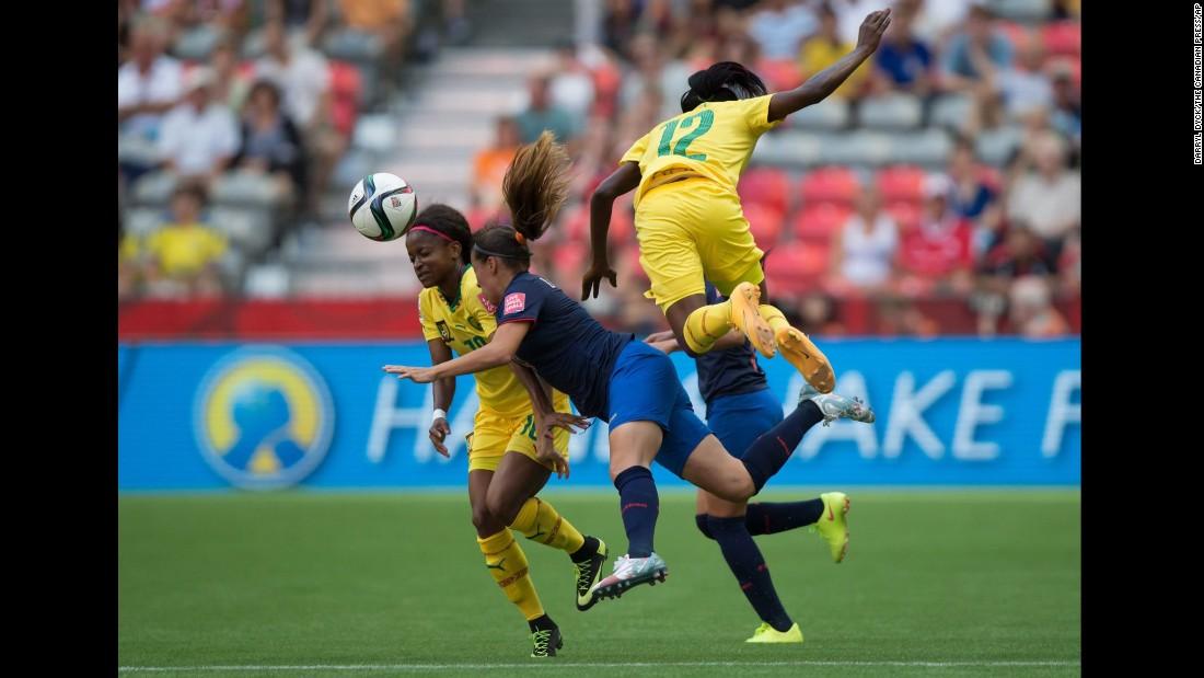 Cameroon's Jeannette Yango, left, and Claudine Meffometou Tcheno, right, collide with Ecuador's Giannina Lattanzio.