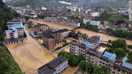 A photo taken on May 27, 2015 shows a residential area submerged in flood water after strong rainstorms hit Leishan county in the Qiandongnan Miao and Dong Autonomous region, in southwest China's Guizhou province, after heavy rainstorms hit the area. Heavy rain which caused mudslides and flooding in southern and central China has left at least 35 people dead and another 13 missing, the official Xinhua news agency reported on May 24. Torrential rain -- the worst for 40 years in some parts of the country -- has hit at least six provinces, according to state media and the government. AFP PHOTO / STRINGER