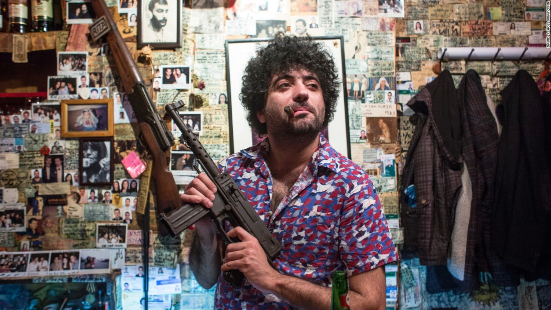 A man poses with a gun at Abu Elie, a bar in Beirut, Lebanon known for decor featuring military paraphernalia and communist iconography.