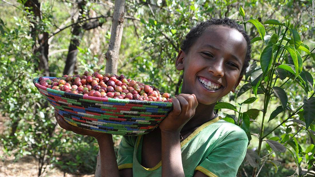 Dukale's daughter shows off a bowl of coffee cherries.