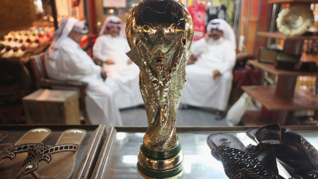 Men at a shoemaker's stall sit by a replica of the World Cup trophy soon after the hosting award brought announcements of a wide variety of infrastructure projects, including the construction of new stadiums and roads.