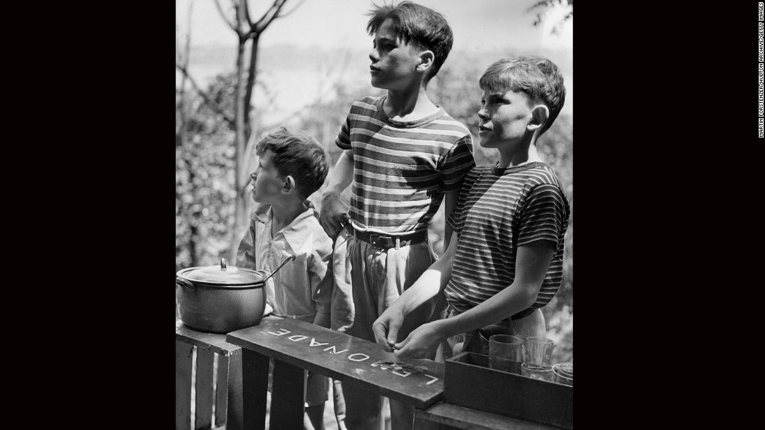 Three boys stand outdoors, working at a lemonade stand circa 1945.
