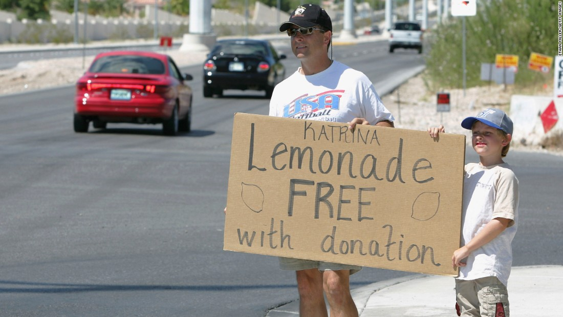 Las Vegas Metropolitan Police Department Detective Dean O'Kelley and his son Noah hold a sign alerting motorists of their offer of lemonade in exchange for donations for Hurricane Katrina relief in September 2005.