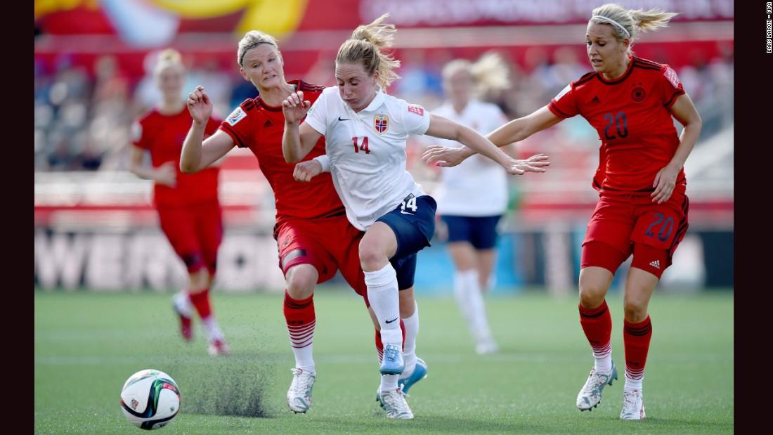 Ingrid Schjelderup of Norway is challenged by two German defenders.