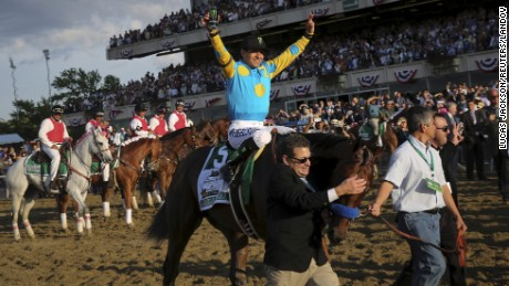 Jockey Victor Espinoza, aboard American Pharoah, celebrates after winning the 147th running of the Belmont Stakes as well as the Triple Crown, in Elmont, New York.