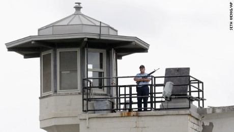 A prison employee stands guard on a tower at the Clinton Correctional Facility on June 10. Police were resuming house-to-house searches near the maximum-security prison.