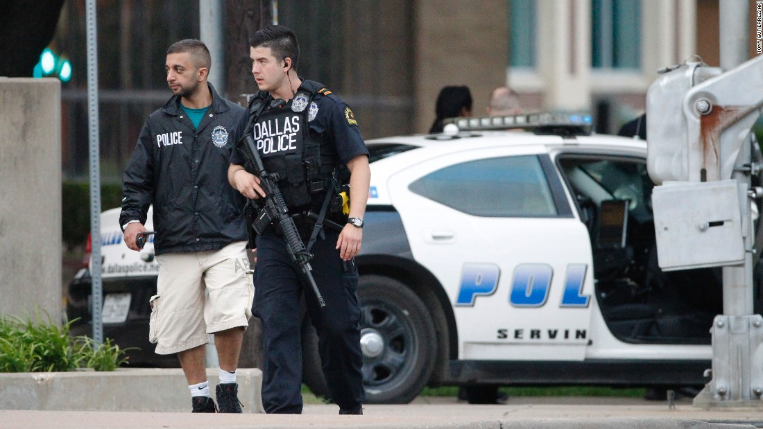 Police officers walk down Belleview Street on June 13, one block away from Dallas Police Department headquarters, as they search the area after the early morning attack on the building.
