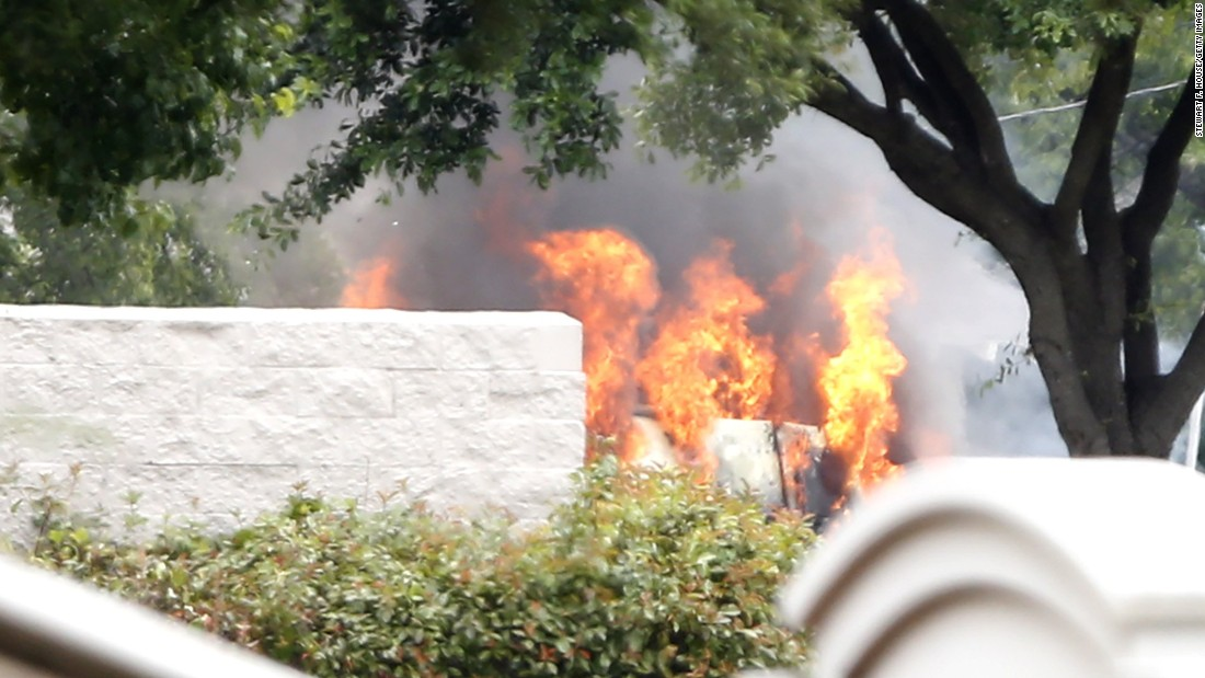 The van used by a lone shooter to attack and then flee Dallas Police Headquarters catches fire outside a fast-food restaurant on June 13,  in Hutchins, Texas. Authorities used controlled charges to discharge pipe bombs in the van after the shooter reportedly unleashed multiple rounds and planted explosive devices around the station before leading police on a chase that ended in a standoff in the parking lot of the restaurant.