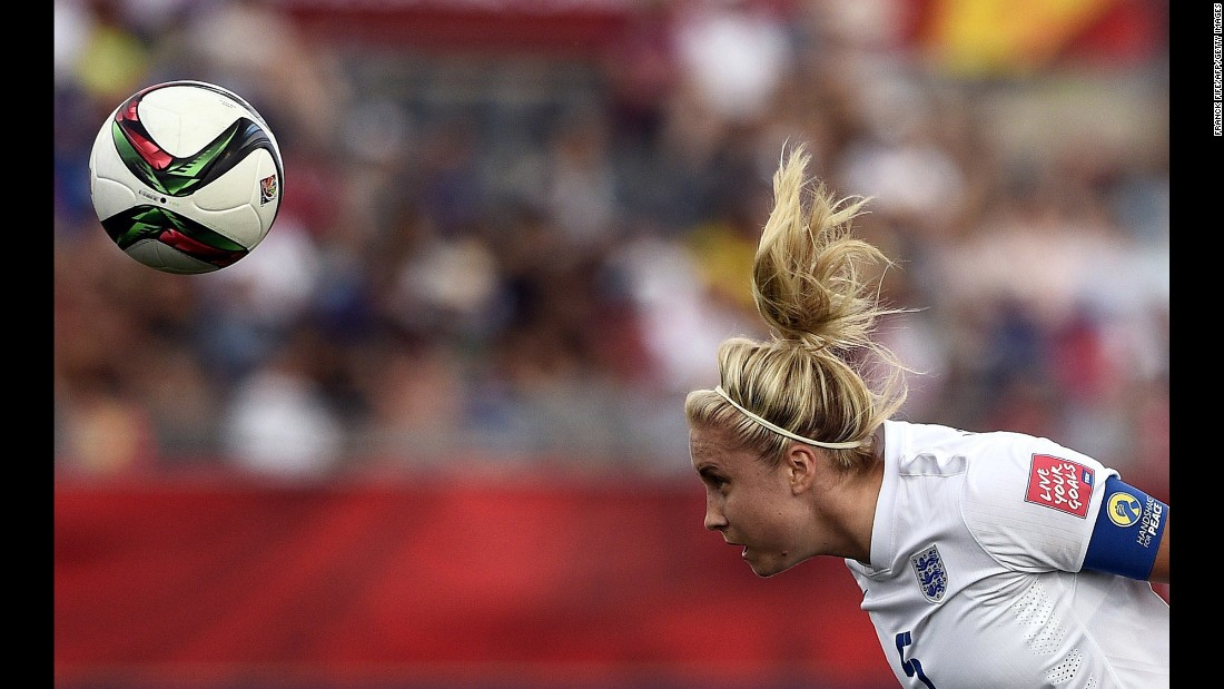 England defender Laura Bassett heads the ball.