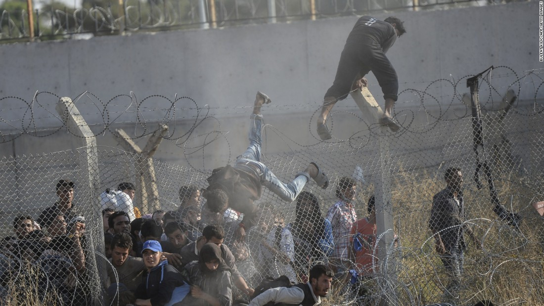 "A man climbs over the fence as others force their way through a hole in the fencing. ""Thousands of them came inside in an illegal way. They broke down the fences and they came inside,"" Kilic told CNN."