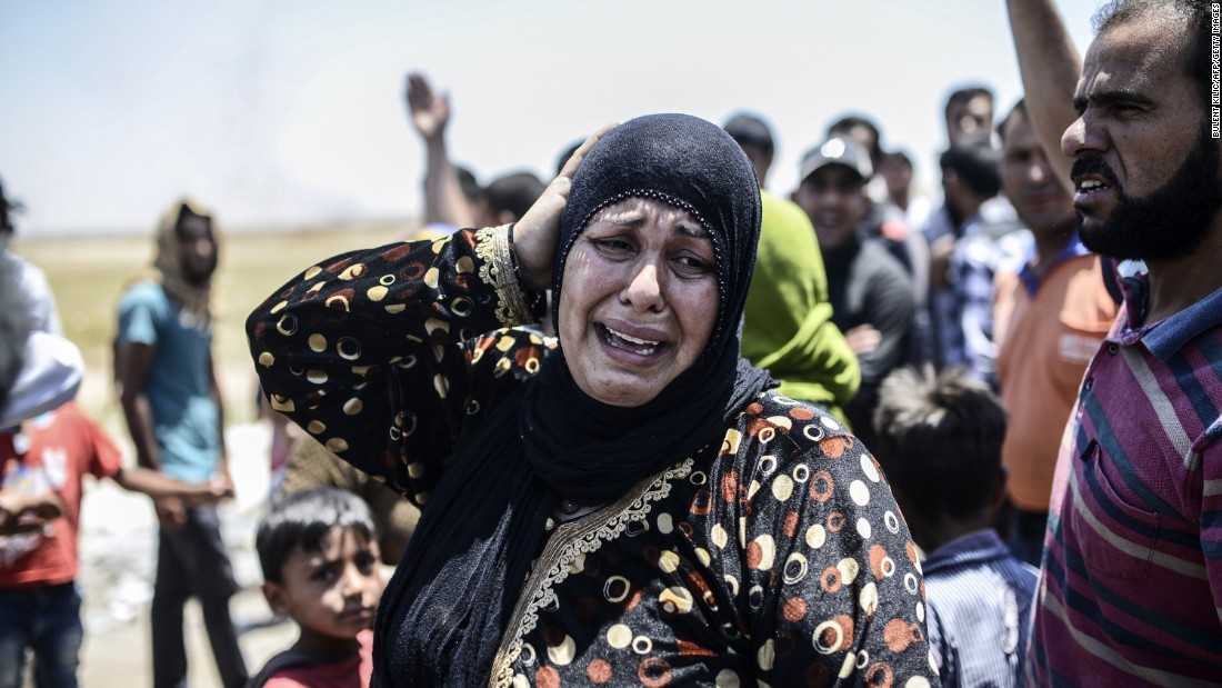 A Syrian woman cries after an airstrike hit the eastern part of Tal Abyad, Syria, as thousands massed at the nearby border crossing to escape escalating fighting.