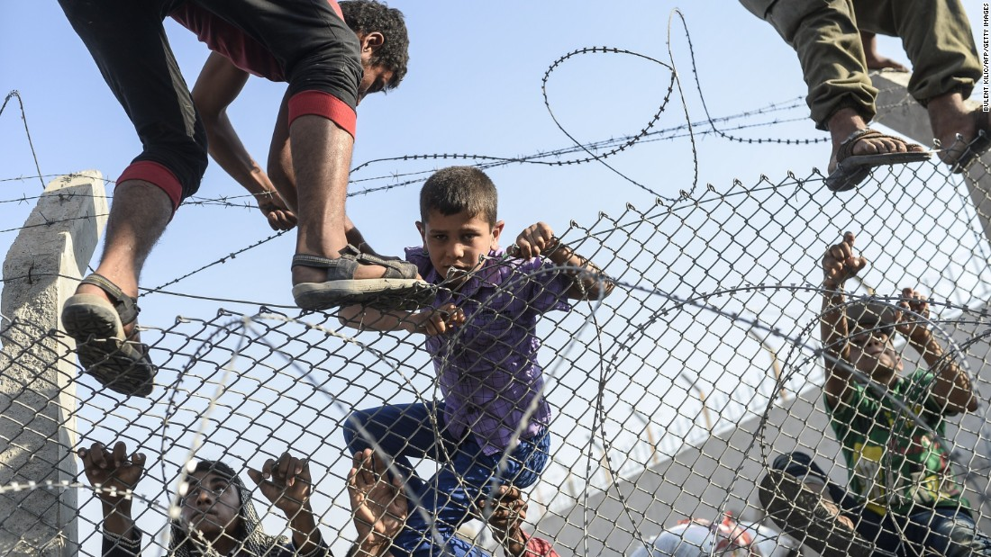 A boy is helped as he climbs over the border fence.