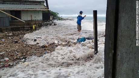 This photo taken on March 3, 2014 shows a resident surrounded by the on-rushing high tide energized by a storm surge that damaged a number of homes across Majuro.   It was the third inundation of the Marshall's capital atoll in the past 12 months. The Marshall Islands has put climate change at the top of its political and diplomatic agenda and officials saw the recently held Cartagena Dialogue as an opportunity to gather momentum.      AFP PHOTO / Karl Fellenius        (Photo credit should read Karl Fellenius/AFP/Getty Images)