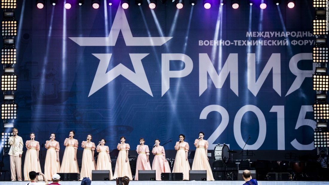 Performers sing a Russian patriotic song on stage.
