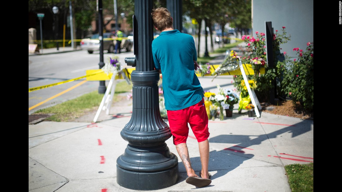 A man leans against a light pole as he visits a memorial in Charleston on June 18.
