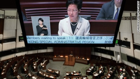 A TV screen shows Hong Kong Chief Secretary Carrie Lam as she addresses the city's legislature in Hong Kong on June 17, 2015.