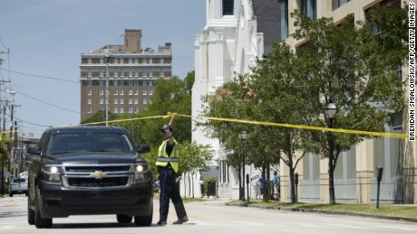 A police officer directs a police vehicle in front of the Emanuel AME Church on June 18.