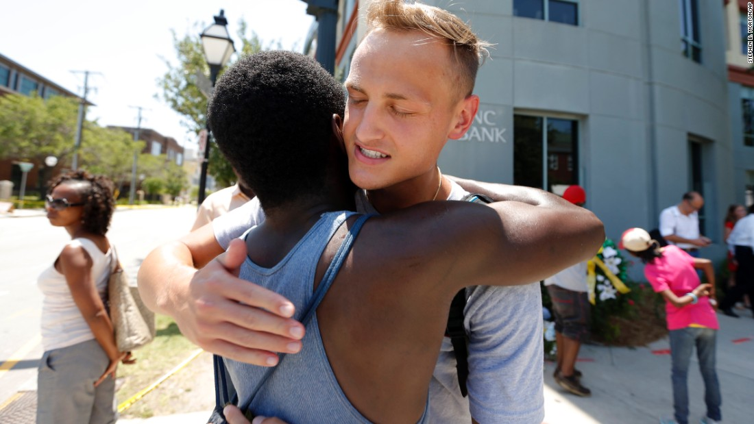Tyler Francis, right, hugs Shondrey Dear after praying together June 18 at a makeshift memorial near the Emanuel AME Church.