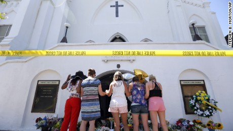 A group of women pray together at a makeshift memorial on the sidewalk in front of the Emanuel AME Church, on Thursday, June 18, in Charleston, South Carolina.  (AP Photo/Stephen B. Morton)