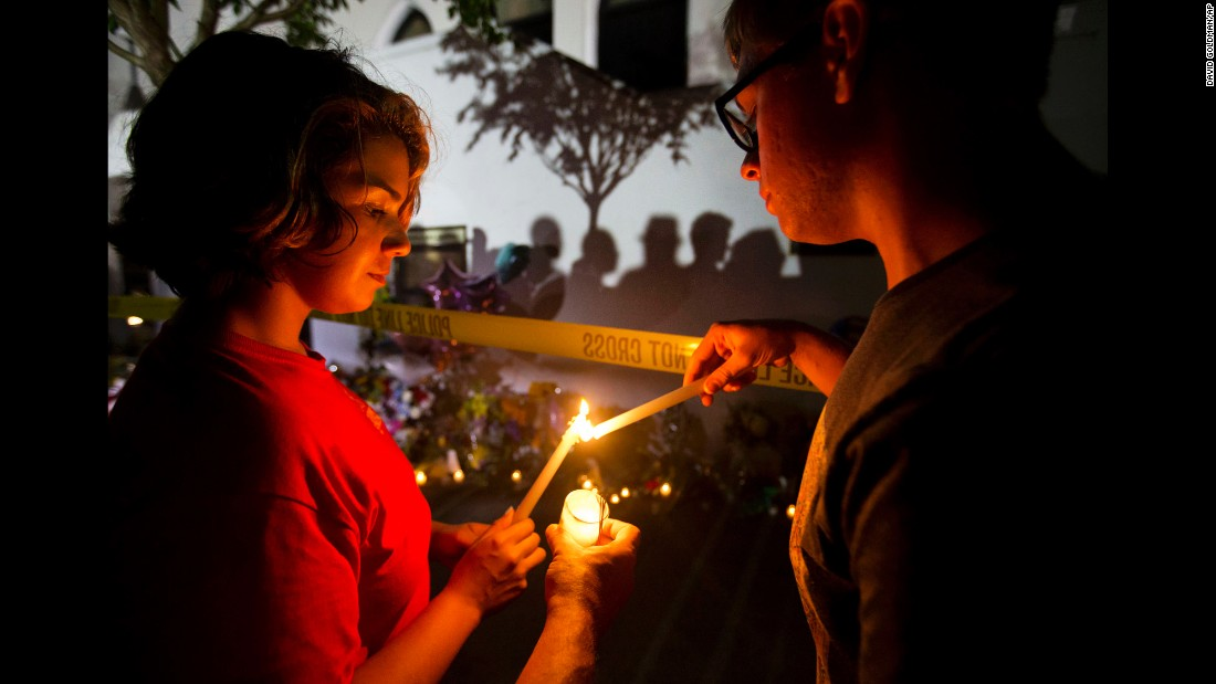 Olina Ortega, left, and Austin Gibbs light candles at a sidewalk memorial in front of Emanuel AME Church on June 18.