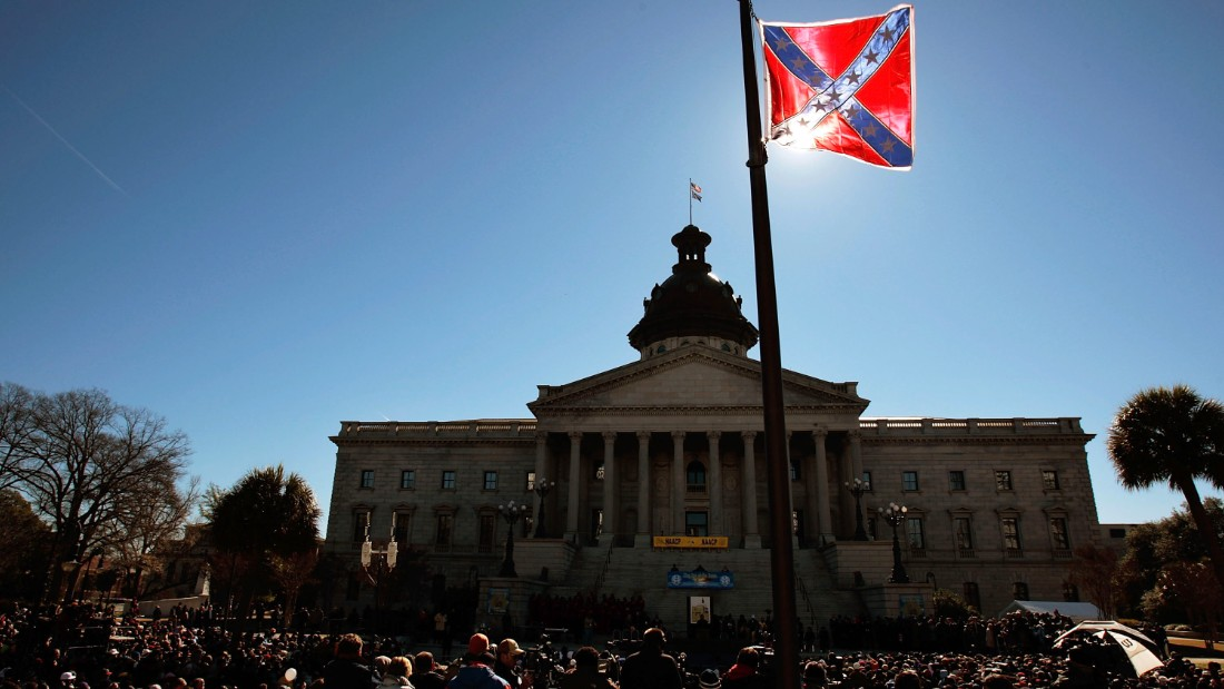 COLUMBIA, SC - JANUARY 21:  A Confederate flag that's part of a Civil War memorial on the grounds of the South Carolina State House flies over a Martin Luther King  Day rally January 21, 2008 in Columbia, South Carolina.  All three major Democratic candidates for President spoke to a large crowd on the state house grounds.  (Photo by Chris Hondros/Getty Images)