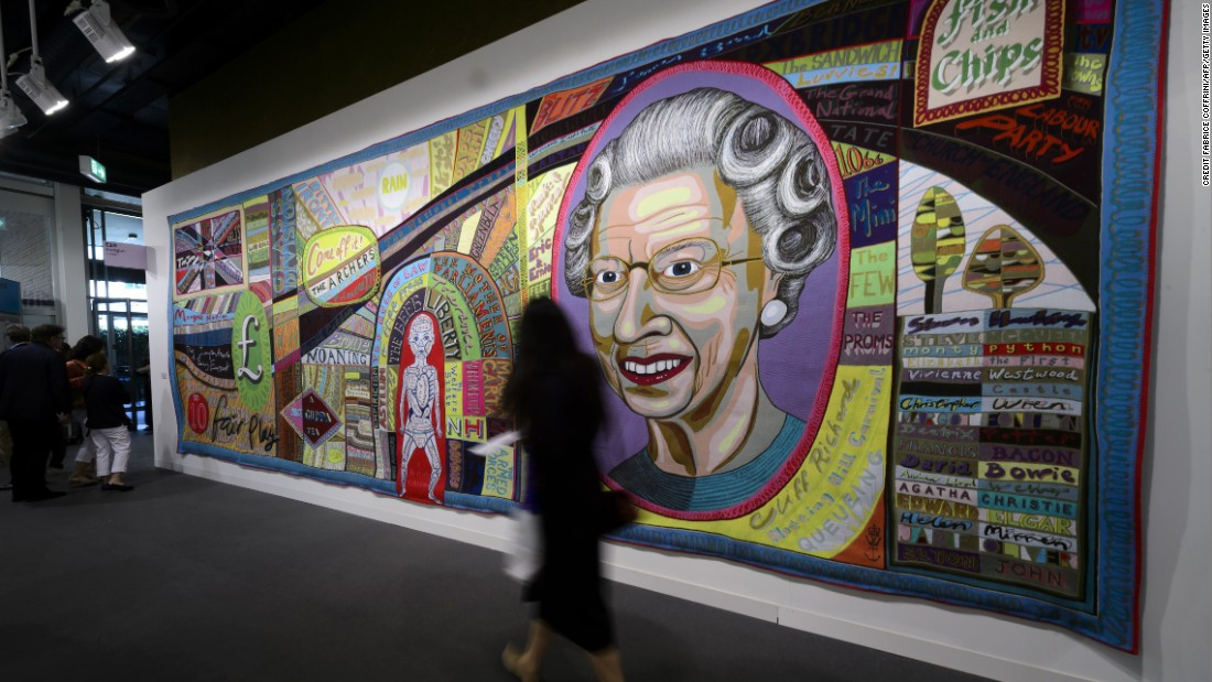 A woman walks in front of an artwork by British artist Grayson Perry entitled 'Comfort Blanket'.
