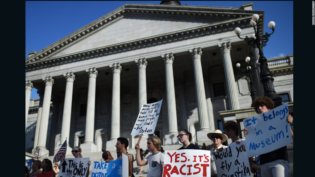Protesters stand on the South Carolina State House steps during a rally to take down the Confederate flag, on Saturday, June 20, in Columbia.