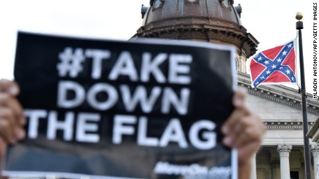 Hundreds of people protest against the Confederate flag (C) during a protest rally in Columbia, South, Carolina on June 20, 2015. The racially divisive Confederate battle flag flew at full-mast despite others flying at half-staff in South Carolina after the killing of nine black people in an historic African-American church in Charleston on June 17. Dylann Roof, the 21-year-old white male suspected of carrying out the Emanuel African Episcopal Methodist Church bloodbath, was one of many southern Americans who identified with the 13-star saltire in red, white and blue.