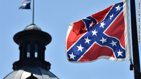 The South Carolina and US flags are seen flying at half-staff behind the Confederate flag erected in front of the State Congress building in Columbia, South Carolina on June 19, 2015. Police captured the white suspect in a gun massacre at one of the oldest black churches in Charleston in the United States, the latest deadly assault to feed simmering racial tensions. Police detained 21-year-old Dylann Roof, shown wearing the flags of defunct white supremacist regimes in pictures taken from social media, after nine churchgoers were shot dead during bible study on Wednesday. AFP PHOTO/MLADEN ANTONOV (Photo credit should read MLADEN ANTONOV/AFP/Getty Images)