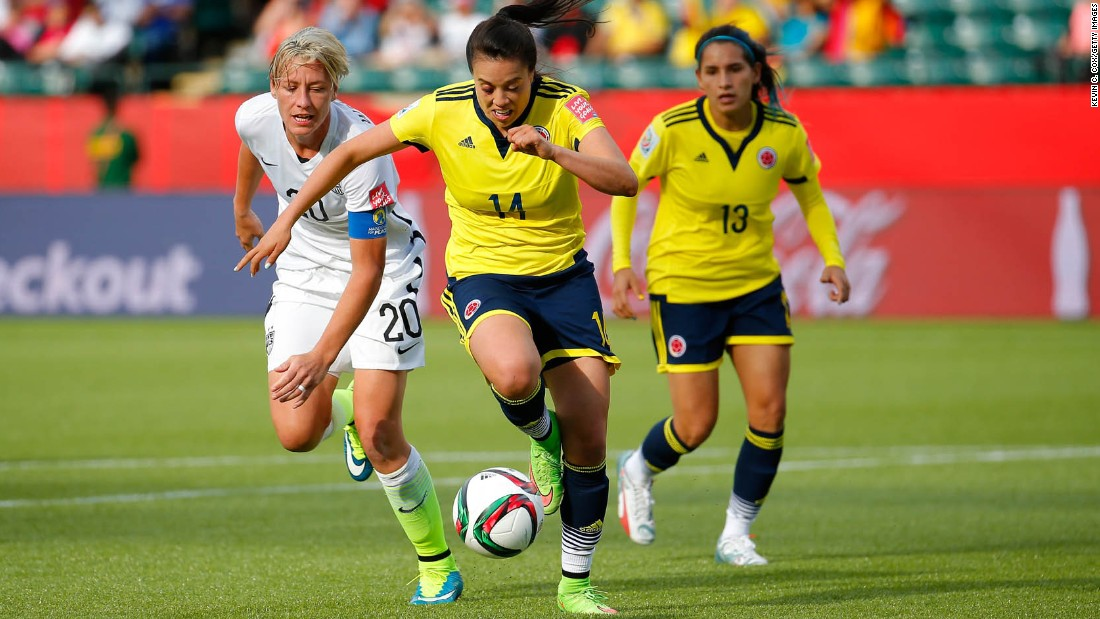 Nataly Arias of Colombia, center, controls the ball near U.S. forward Abby Wambach.