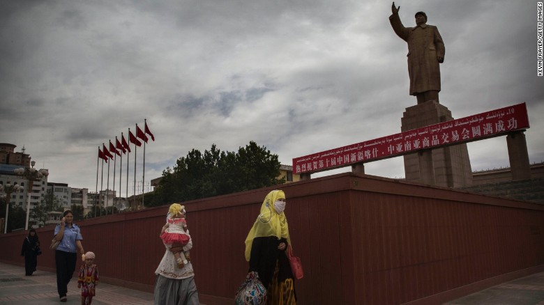 A veiled Muslim Uyghur woman walks passed a statue of Mao Zedong on July 31, 2014 in Kashgar, Xinjiang.