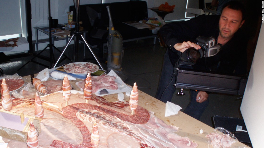 Warner, seen here shooting one of his foodscapes, describes himself as a photographic artist who makes landscapes out of food, although he does create scenes out of other materials like clothes and stationary.