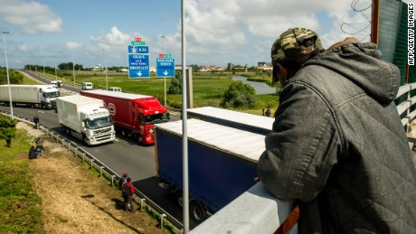 Migrants wait along the A16 highway as they try to access the Channel Tunnel on June 23, 2015 in Calais, northern France. AFP PHOTO PHILIPPE HUGUEN (Photo credit should read PHILIPPE HUGUEN/AFP/Getty Images)