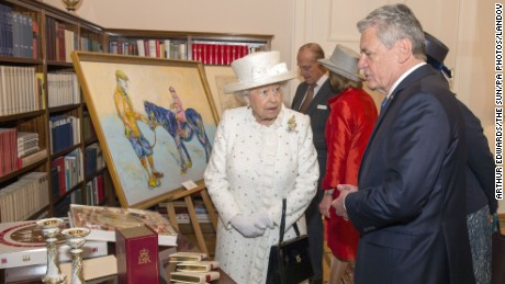 "Queen Elizabeth II and Germany's Federal President Joachim Gauck exchange gifts at his official Berlin residence, Bellevue Palace, on the first full day of her state visit to Germany. A gift of a stylized painting of the Queen sat on a pony prompted the monarch to declare ""that's a funny color for a horse"" when the German president gave her the artwork."