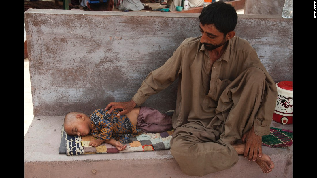A man awaits medical help for his daughter who is suffering from dehydration due to the extreme weather in Karachi on June 24.