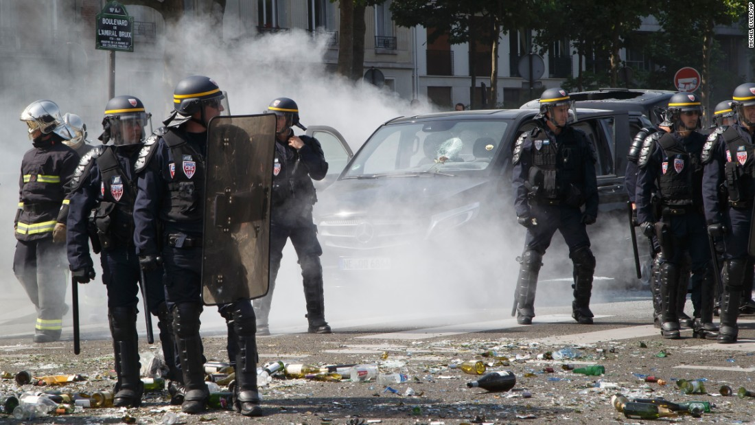 Police stand next to a burned-out car during the Paris protest on June 25.