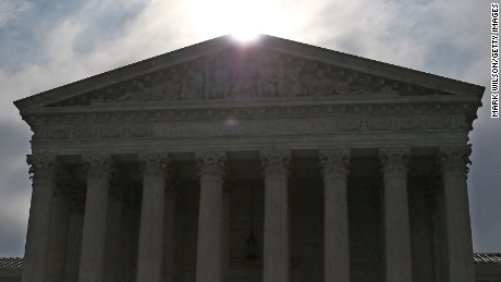 The early-morning sun rises behind the Supreme Court building June 18, 2015 in Washington, D.C.