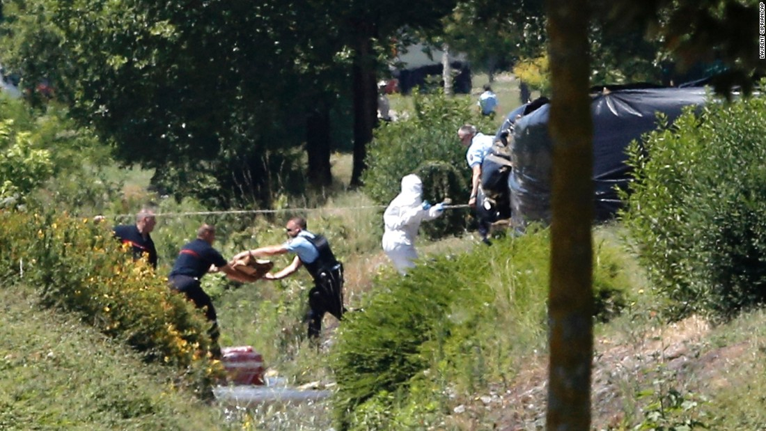 Investigators work at the enclosed area where a decapitated body was discovered at the Saint-Quentin-Fallavier factory on June 26. The severed head was found with a message, Hollande said.