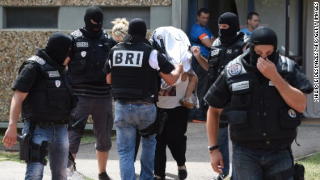 Special forces of France's Research and Intervention Brigades (BRI) escort an unidentified woman and a child as they leave the building housing the apartment of a man suspected of carrying out an attack in Saint-Priest near Lyon on June 26, 2015.