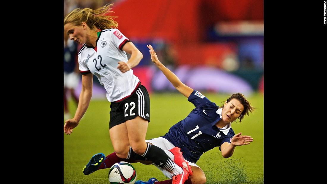 French midfielder Claire Lavogez slides in on  German midfielder Tabea Kemme.