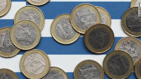 Euro coins over Greek flag