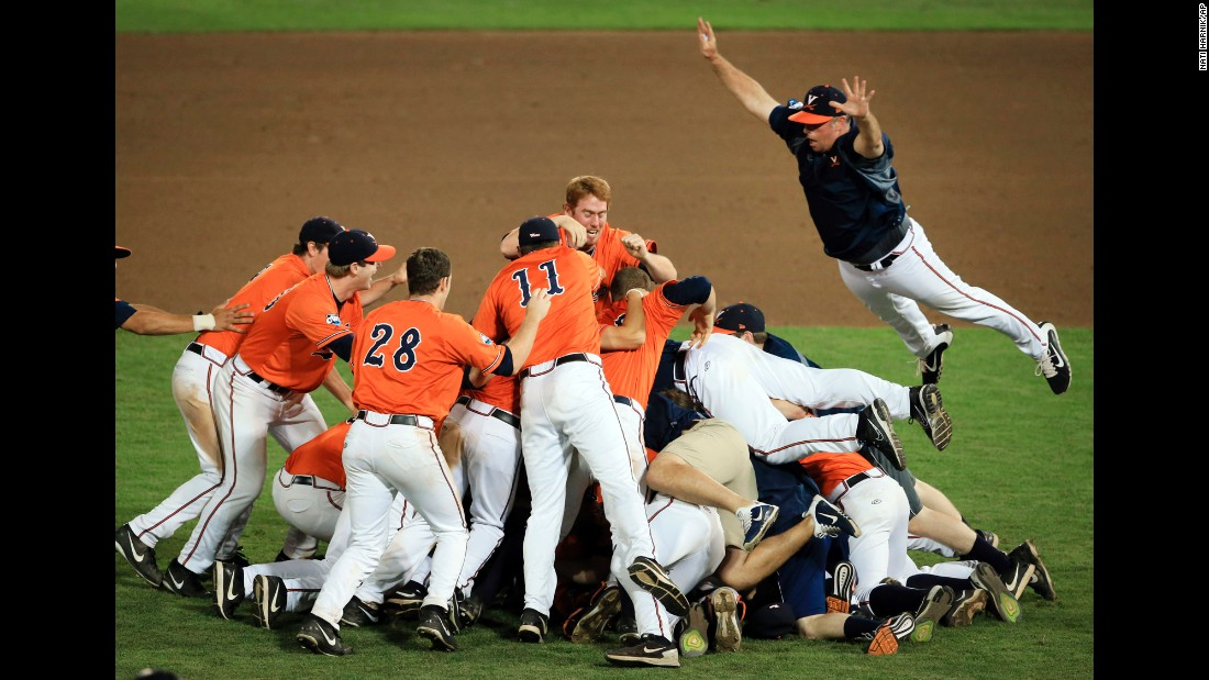 Assistant coach Matt Kirby jumps onto a pile of players after Virginia defeated Vanderbilt to win the College World Series on Wednesday, June 24. It was the first national title for Virginia, which lost to Vanderbilt last year in the championship series.