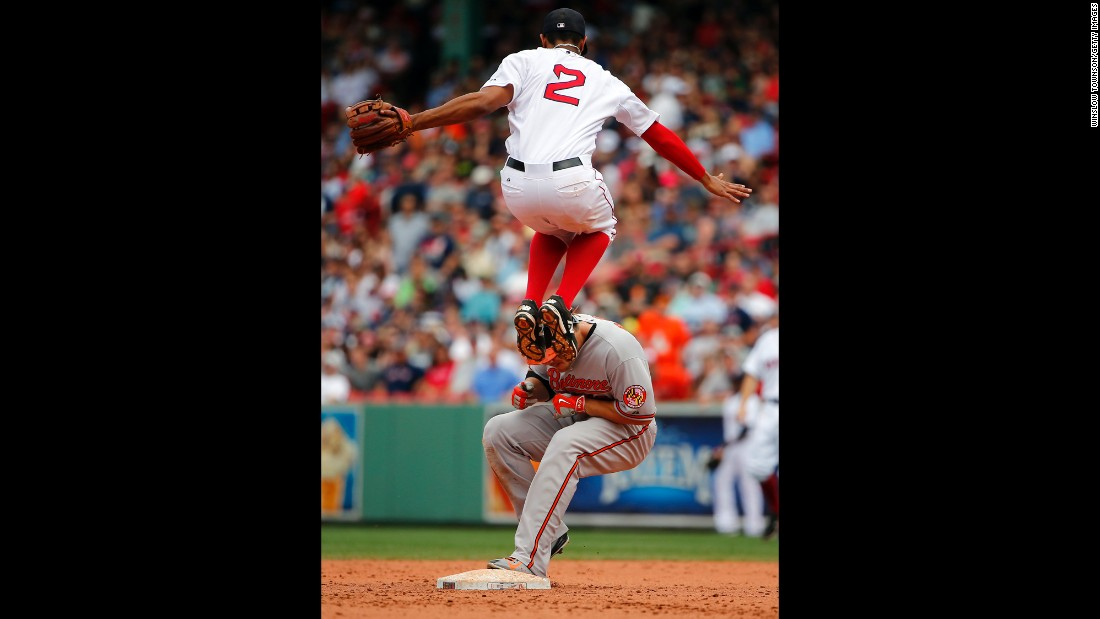 Boston's Xander Bogaerts leaps over second base to avoid Baltimore's Chris Davis, who had just hit a double on Thursday, June 25.