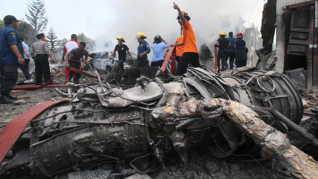 Firefighters work at the crash site in Medan.