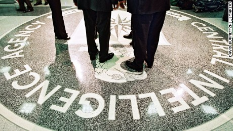 President George W. Bush, Central Intelligence Agency Director George Tenet and others stand on the seal of the Agency March 20, 2001 at the CIA Headquarters in Langley, Virginia. Bush toured the facility and met some of the Agency''s employees.
