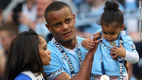 Vincent Kompany the captain of Manchester City lifts his daughter Sienna alongside his wife Carla following the Barclays Premier League match between Manchester City and Queens Park Rangers at Etihad Stadium on May 13, 2012 in Manchester, England. (Photo by Alex Livesey/Getty Images