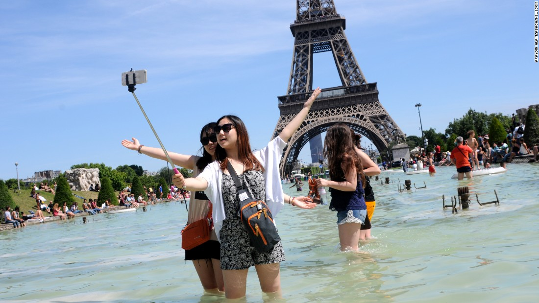 People in Paris wade in an ornamental lake near the Eiffel Tower on Sunday, June 28.
