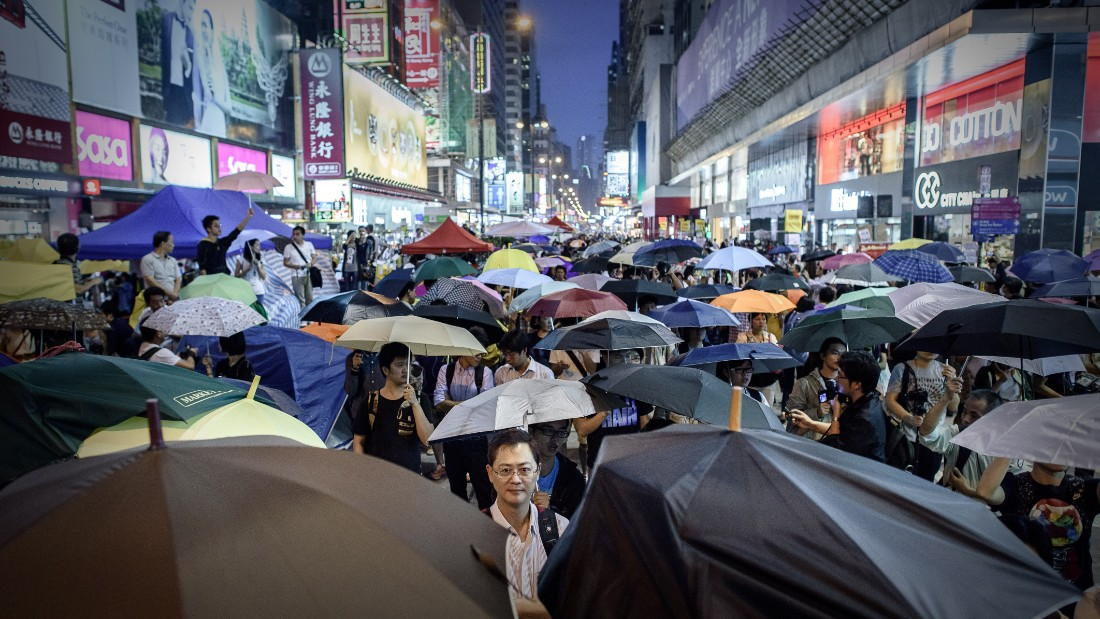 Pro-democracy protesters open their umbrellas to mark one month since they took to the streets, in the Mongkok district of Hong Kong on October 28, 2014. Hong Kong democracy activists on October 28 marked one month of mass protests, calling on supporters to gather for an evening rally wearing the masks they have used to ward off police tear gas and pepper spray. AFP PHOTO / Philippe Lopez        (Photo credit should read PHILIPPE LOPEZ/AFP/Getty Images)