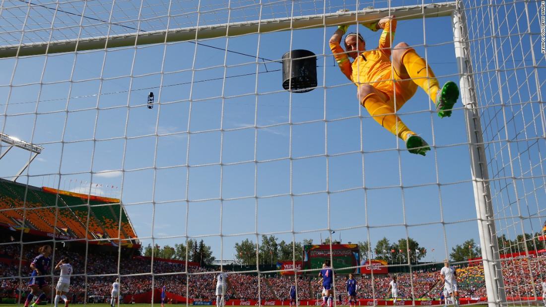 English goalkeeper Karen Bardsley hangs from the crossbar.